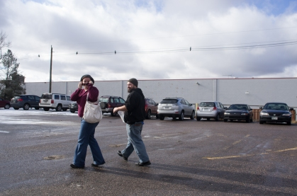 A pair of satisfied customers leave the store with a sack of marijuana.
