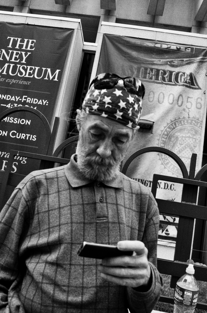 DENVER,Colo-October 4, 2014-A man in patriotic garb checks his phone in front of the Federal Reserve.