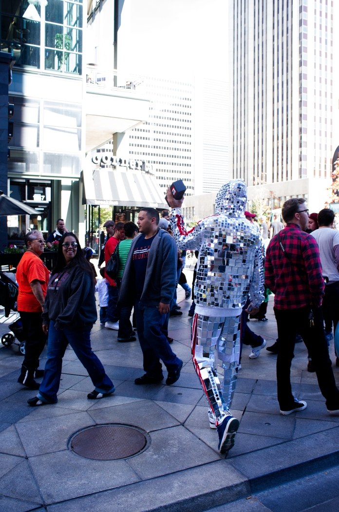 DENVER,Colo.-October 18,2013-A man in a mirror-laden jumpsuit dances to his bluetooth speaker on the 16th Street Mall.